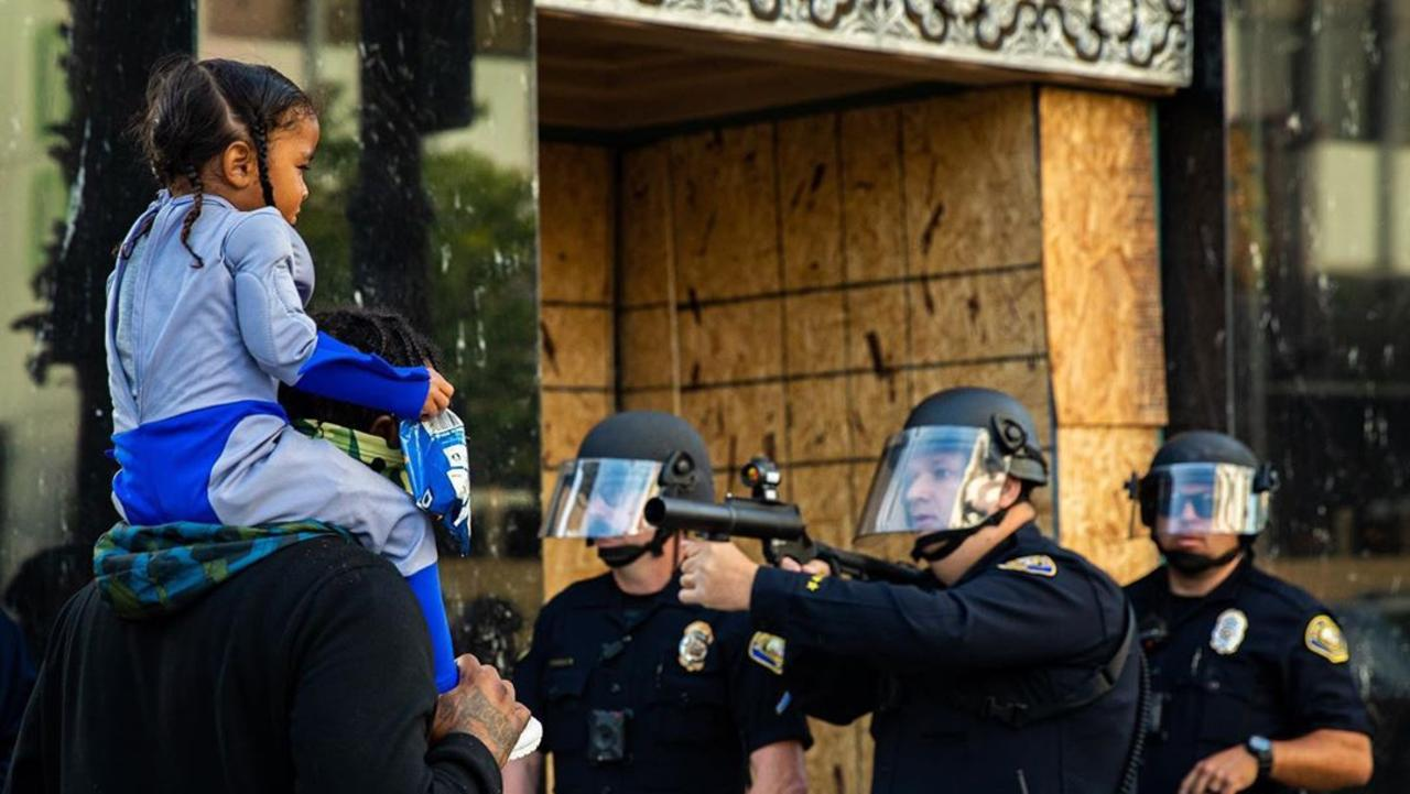 Freelance photographer Richard Grant took this photo of a police officer pointing a rubber bullet gun in front of a man and a child during protests at Long Beach, California. Picture: Richard Grant