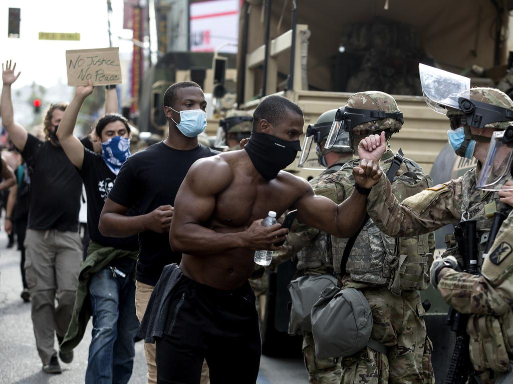 Demonstrators greet members of the National Guard as they march along Hollywood Boulevard. Picture: Ringo H.W. Chiu