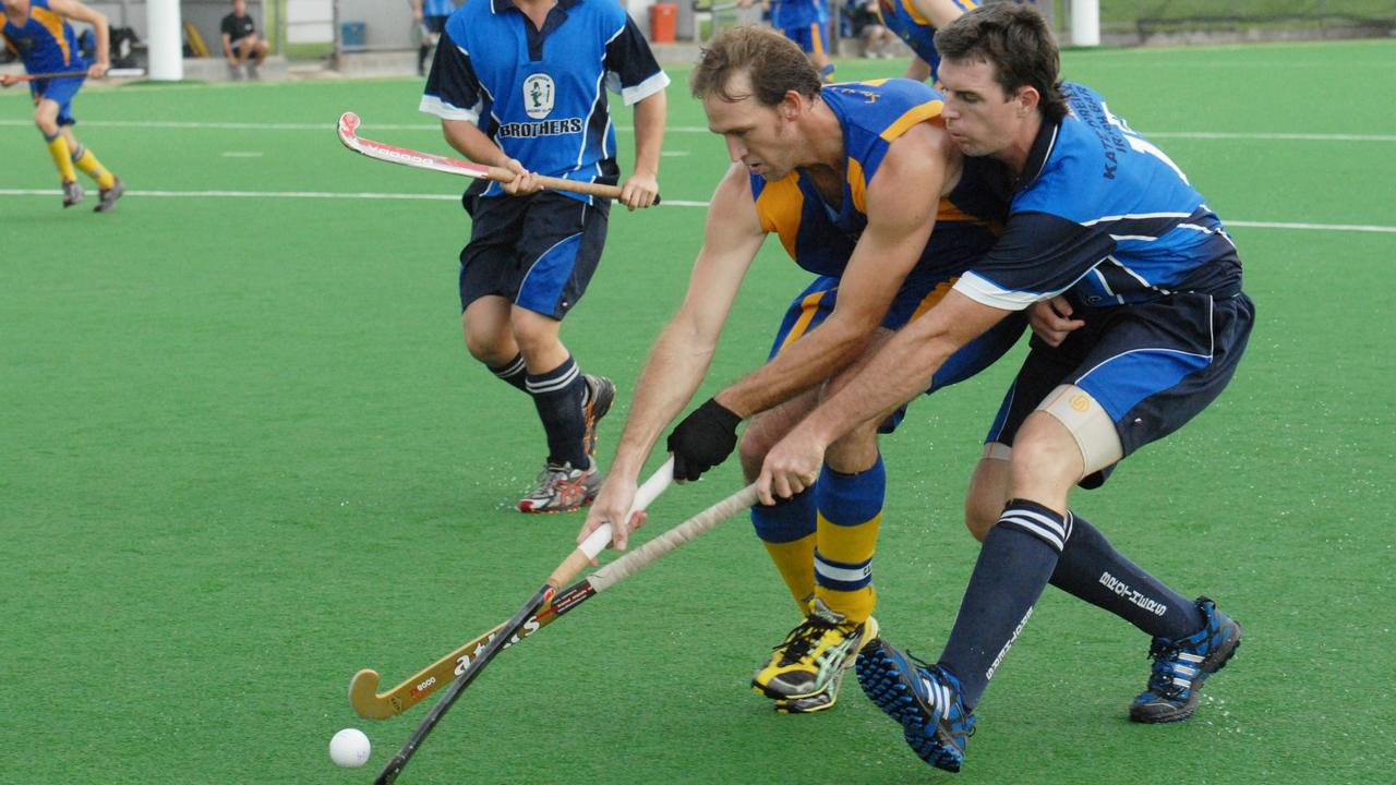 In Mackay hockey Souths Michael Bartlett (left) and brothers Nathan Fitzgerald contest the ball.