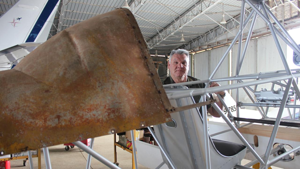 Military Aviation Museum volunteer Dan Holloway shows the yellow paint still visible on the fuselage of the Wackett being restored by the MMAM.