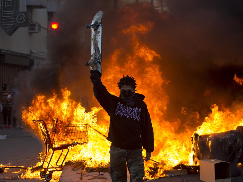 A protester holds a skateboard in front of a fire in Los Angeles during a protest over the death of George Floyd. Picture: Ringo H.W. Chiu