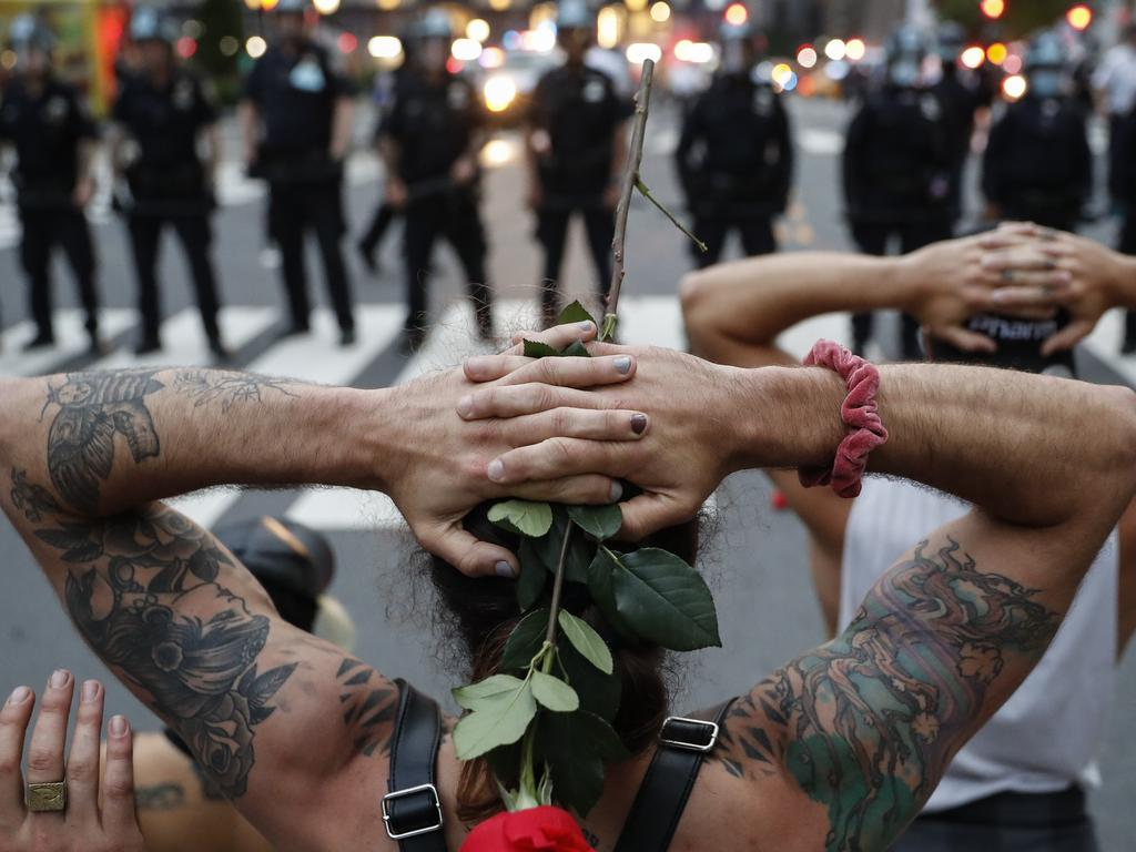 Protesters kneel in front of New York City Police Department officers before being arrested for violating curfew beside the iconic Plaza Hotel. Picture: AP