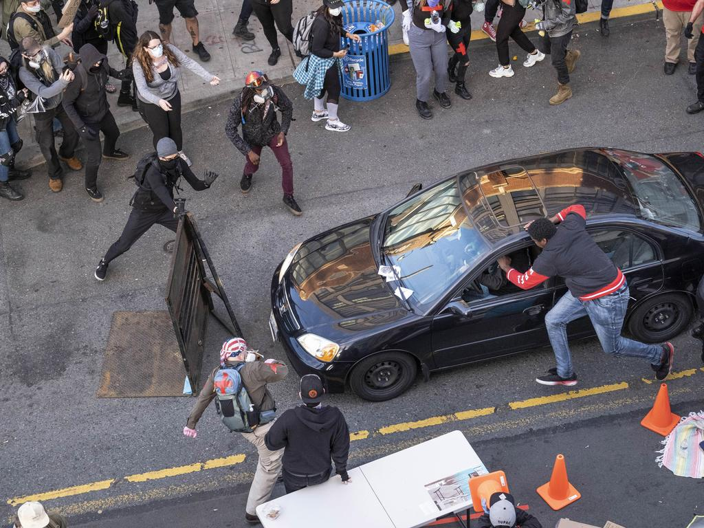 A man drives into the crowd at 11th and Pike, injuring at least one person, before exiting the car and brandishing a firearm in Seattle. Picture: Dean Rutz/The Seattle Times via AP