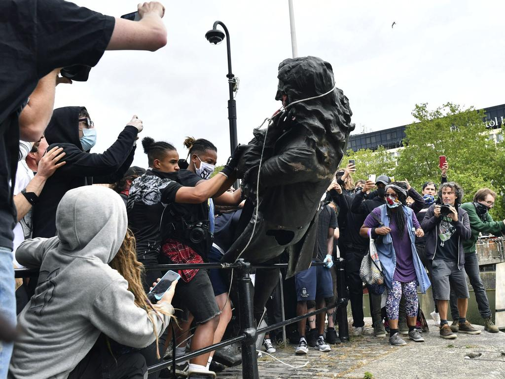 Protesters throw a statue of slave trader Edward Colston into the Bristol harbour. Picture: AP