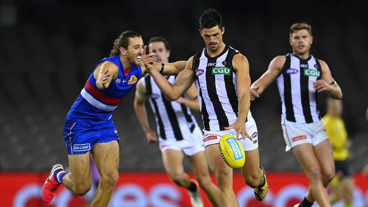 MELBOURNE, AUSTRALIA – MARCH 20: Scott Pendlebury of the Magpies kicks while being tackled by Marcus Bontempelli of the Bulldogs during the round 1 AFL match between the Western Bulldogs and the Collingwood Magpies at Marvel Stadium on March 20, 2020 in Melbourne, Australia. (Photo by Quinn Rooney/Getty Images)