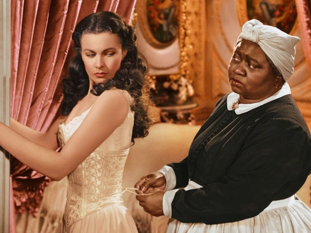 A scene from the 1939 film Gone With the Wind showing Scarlett (Vivien Leigh) being laced into a corset by Mammy (Hattie McDaniel). Picture: Supplied