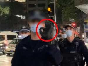 Cop flashes white power symbol