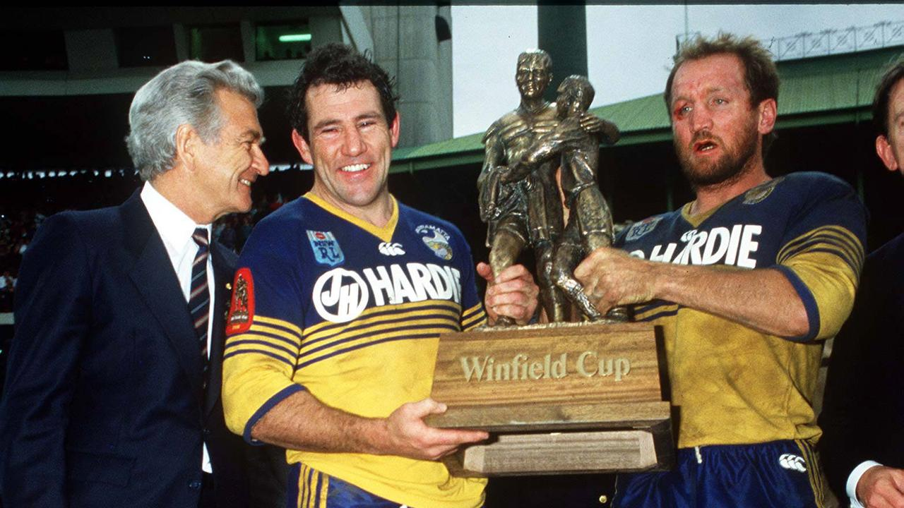 Prime Minister Bob Hawke with Parramatta players Michael Cronin and Ray Price holding the Windfield Cup trophy after Parramatta Eels defeated Canterbury Bulldogs in the 1986 RL grand final at the SFS in Sydney. Pic Action Photographics