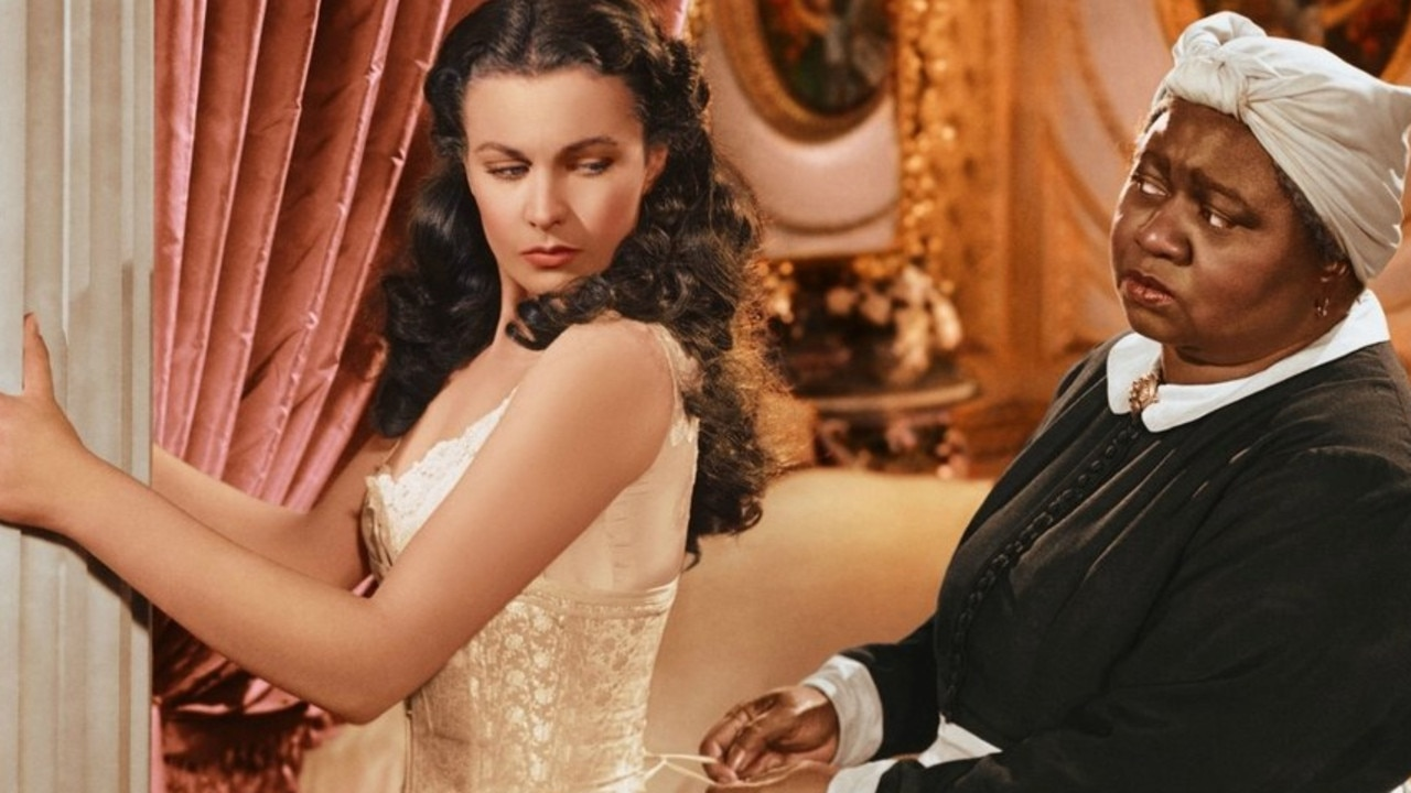 A scene from 1939 film Gone With the Wind showing Scarlett (Vivien Leigh) being laced into a corset by Mammy (Hattie McDaniel).