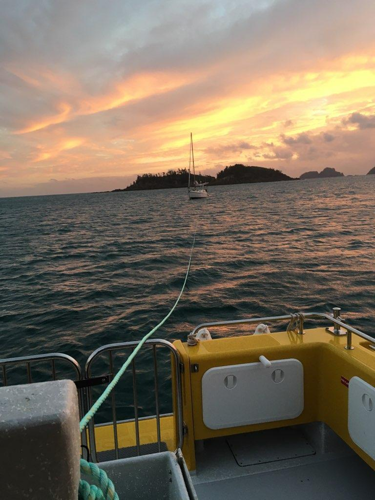 Disabled yacht on tow line at sunrise in Pearl Bay