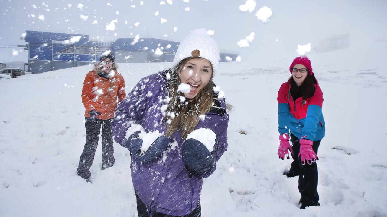 Snow lovers Morgan O'Brien, Ruby Walton and Alicia Lindsay, make the most of the snowfall with a traditional, two-against-one, snowball fight at Mount Buller Alpine Village. Picture: David Caird