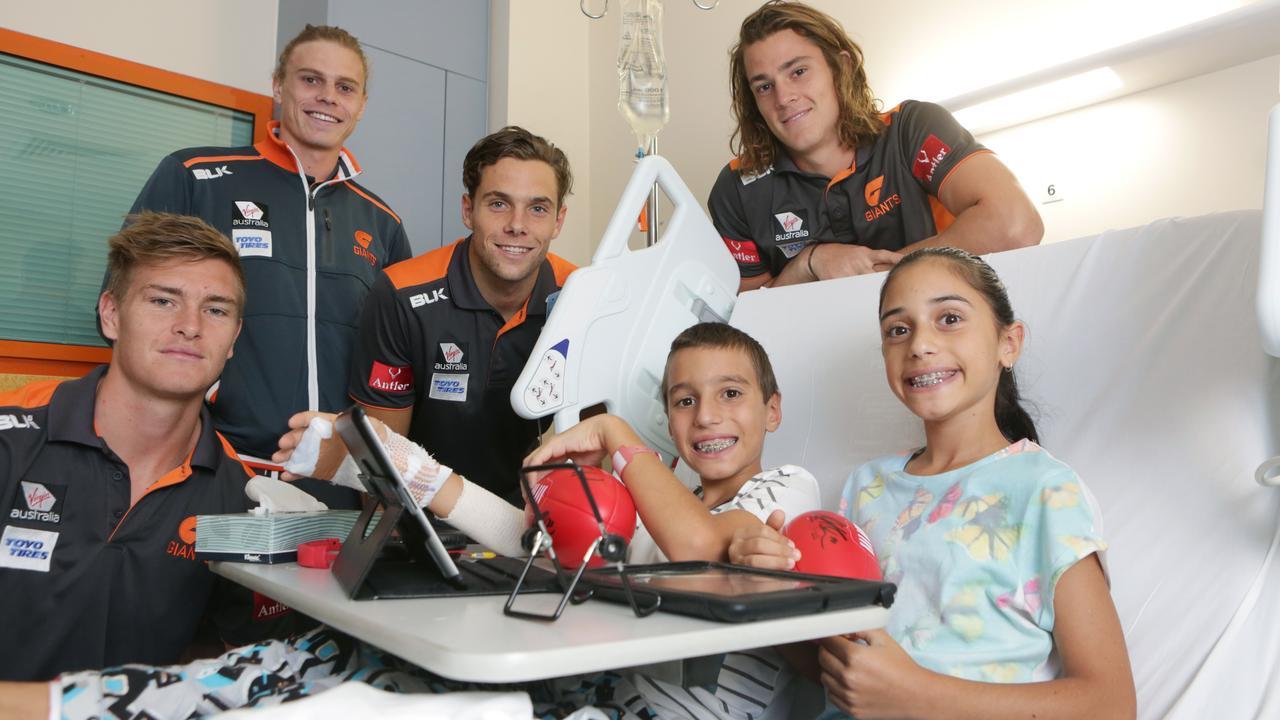 Tomlinson with former GWS teammates visit children at Campbelltown hospital.