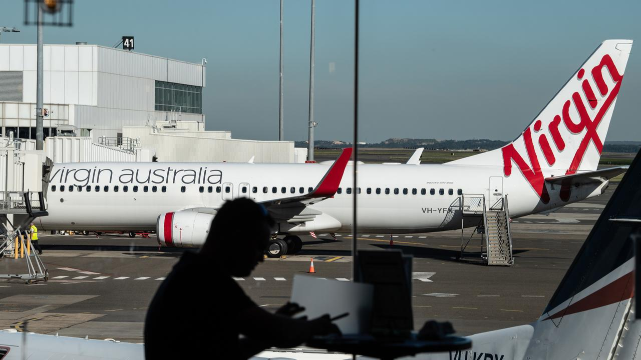 A man sits at a cafe in front of a Virgin Australia aircraft at Sydney Airport, Sydney, Friday, June 19, 2020. (AAP Image/James Gourley)