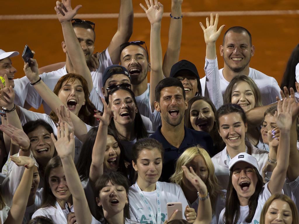Novak Djokovic posing for photographers with tournament volunteers.