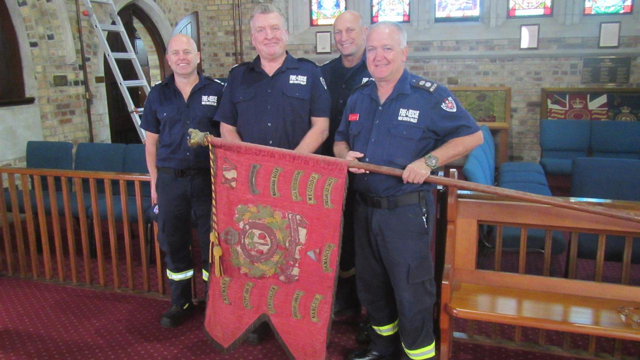 FLYING COLOURS: AN historical guidon was preserved with assistance of Fire & Rescue Lismore. Station officer Ian Grimwood (far right) said C-Platoon were honoured to remove the guidon from its 6m height in St Andrew's Anglican Church. Photo: Supplied