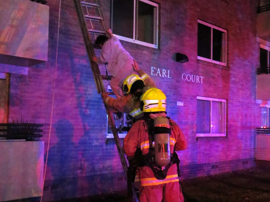 Firefighters rescue one of the occupants of the Villawood unit block.