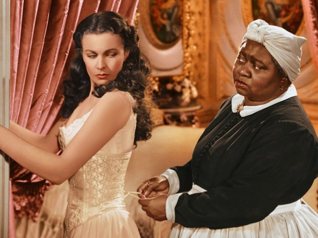 A scene from Gone With the Wind showing Scarlett (Vivien Leigh) being laced into a corset by Mammy (Hattie McDaniel).