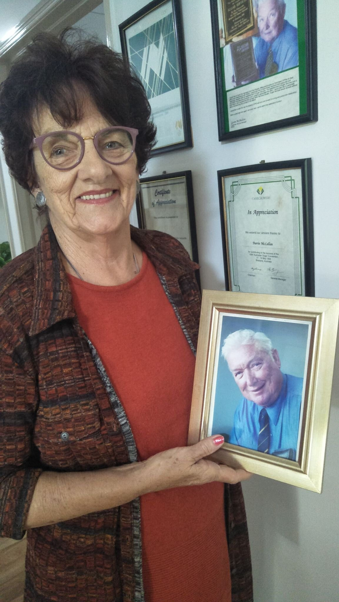 Dot McLellan with a photo of her late husband, Barrie McLellan OAM. Mrs McLellan keeps a wall full of Barrie's achievements in her house in North Bundaberg.