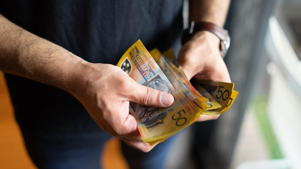 young male counting australian dollars