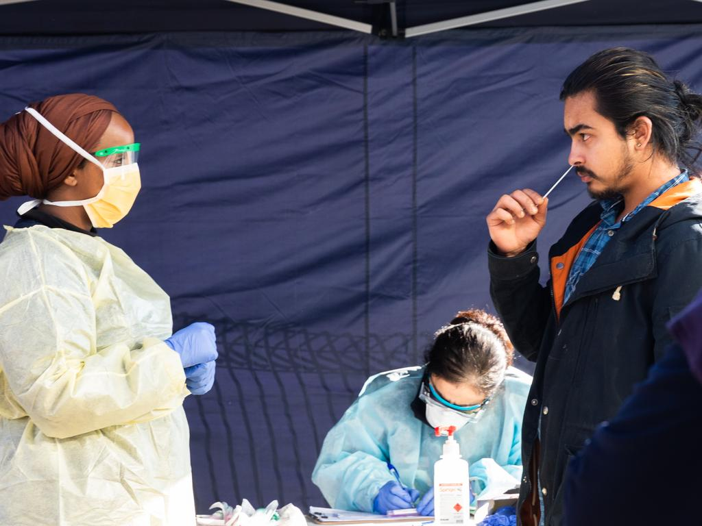 A man conducts a COVID-19 test by inserting a swab in his nose, under the guidance of a member of the testing team at a pop-up testing site in the suburb of Broadmeadows in Melbourne. Picture: Asanka Ratnayake/Getty Images