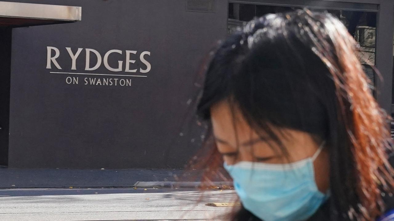 A person wearing a face mask walks past the Rydges on Swanston hotel in Melbourne. Picture: AAP/Scott Barbour