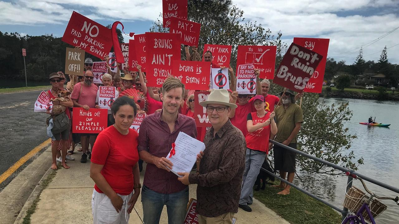 Protesting against paid parking in Brunswick Heads in 2017, Juliana Harmsen and Zac Tooth from Brunswick Heads Chamber of Commerce hand over the anti-paid parking petition containing 4,500 signatures to Byron Shire Councillor Paul Spooner.
