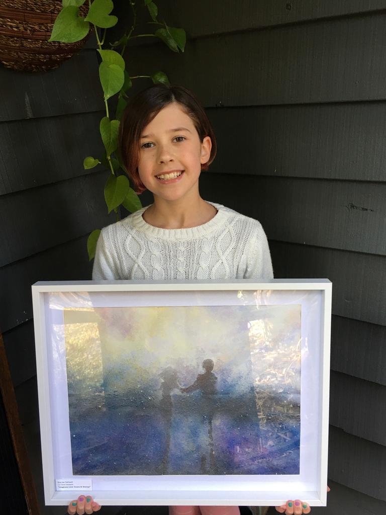 Violet Cann holding Sherree Halliwell's winning artwork