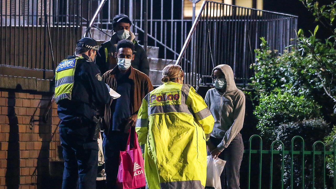 Police talk to residents outside a newly locked-down apartment block in Melbourne. Picture: Ian Currie