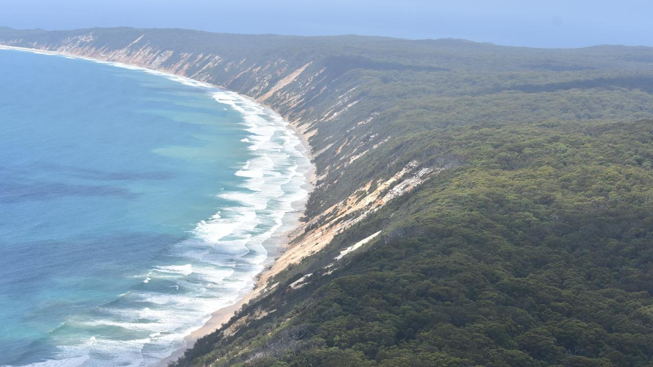 HIGH TIDE: Surf laps at the base of the coloured sand dunes between Rainbow Beach and Double Island Point.