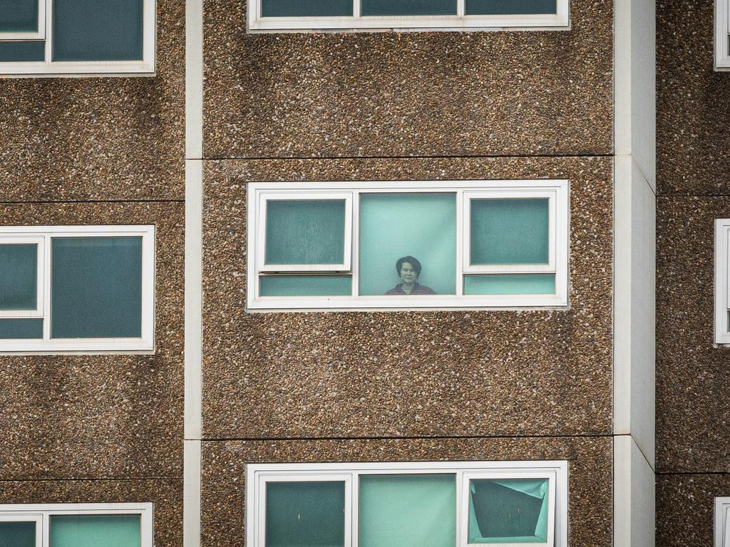 A lone woman looks out the window of her apartment at the North Melbourne public housing flats. Picture: Asanka Ratnayake/Getty Images