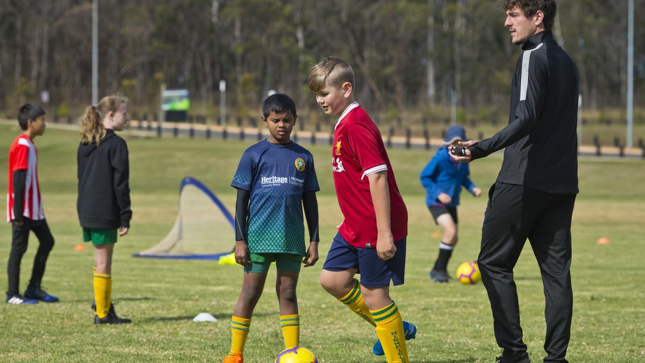 Viren Sevakumar (left) and Tom Pezet work through a drill with coach Mirko Crociati during the Brisbane Roar Academy Highfields FC July holiday camp.