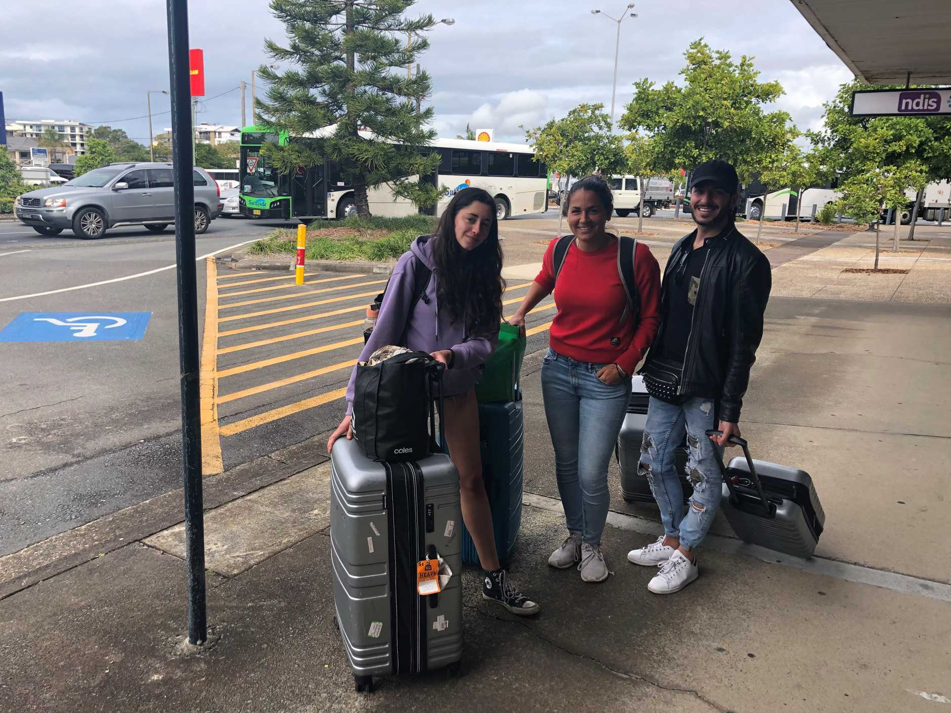 Italian backpackers Camille Bena, Miryam Biavaschi and Flavio Perrino are waiting to cross the Queensland border.