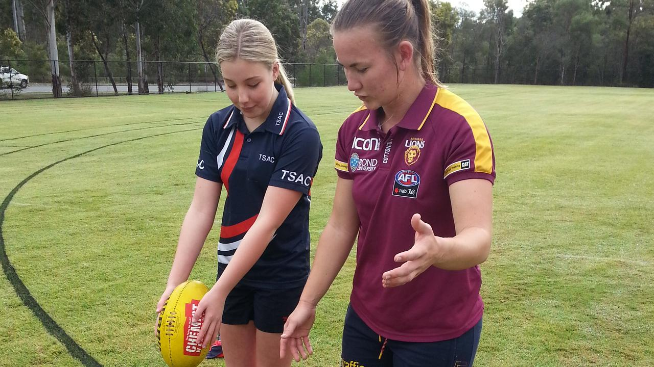 Brisbane Lions footballer Shannon Campbell gives Springfield Anglican College student Olivia Willcox some kicking tips. Picture: David Lems