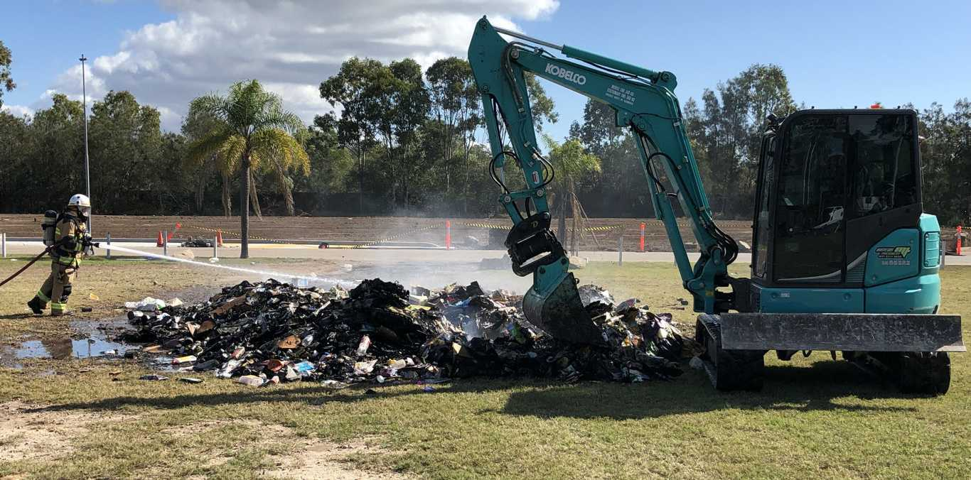 Fire crews from the Torquay station dampen hot spots in the pile of rubbish which caught alight in the back of a garbage truck.