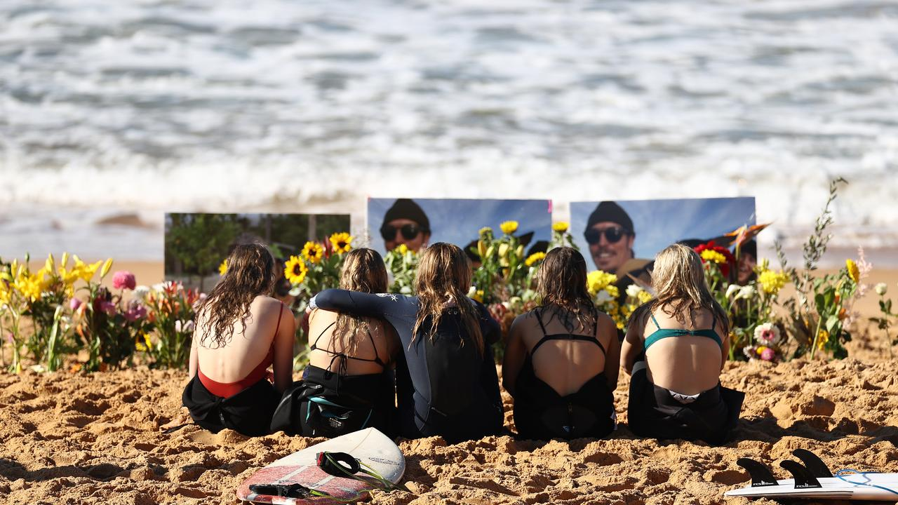 Friends pay their respects in memory of Alex 'Chumpy' Pullin at North Narrabeen Beach. Picture: Ryan Pierse/Getty Images