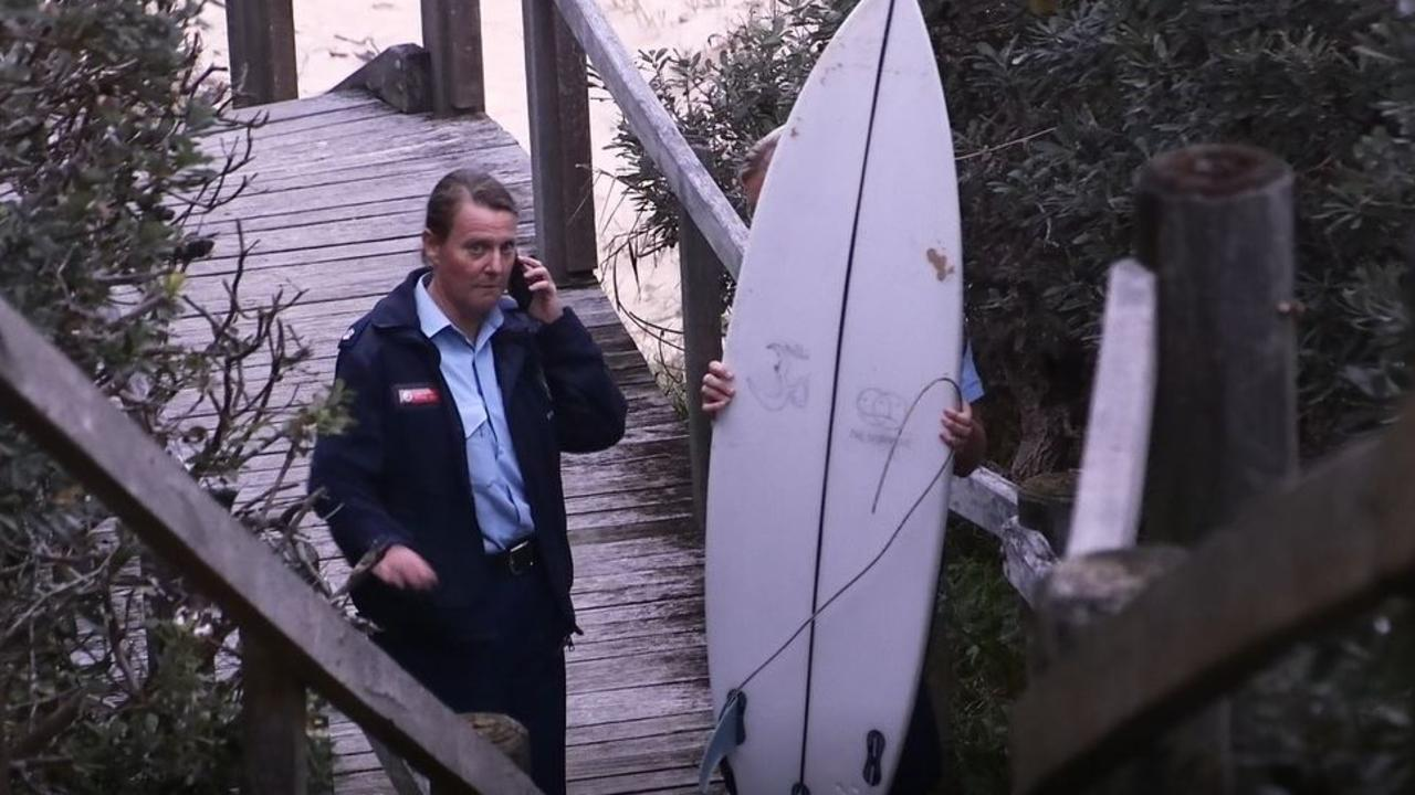 Police with the surfboard ridden by Mani Hart-Deville when he was attacked by a shark at Wilsons Headland on Saturday, 11th July, 2020.