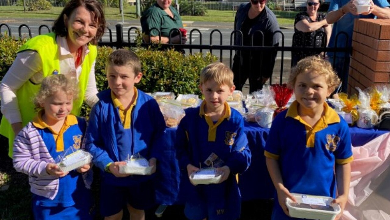 Mackay West State School teacher aide Donna Caroll with students (from left) Teneal Palmer, Caden Bradley, Lake Moffatt and Nate Nicholls at the bake stall. Picture: Contributed.
