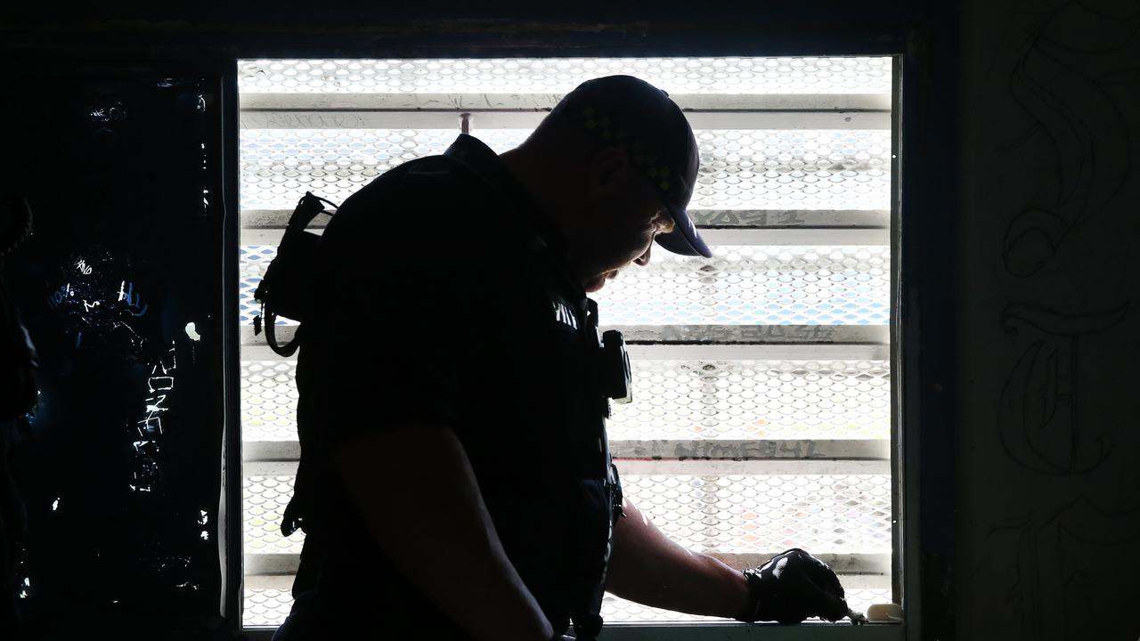 A Corrective Services officers checks the seal on a window for contraband during a raid on cells at Silverwater Jail. Picture: Richard Dobson