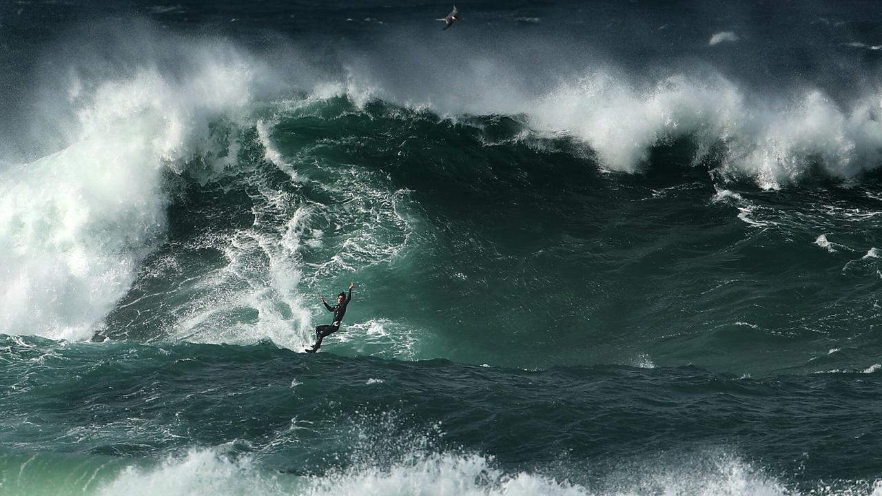 A couple of guys take turns riding a jet ski while the other surfs the huge swell. Picture: John Grainger