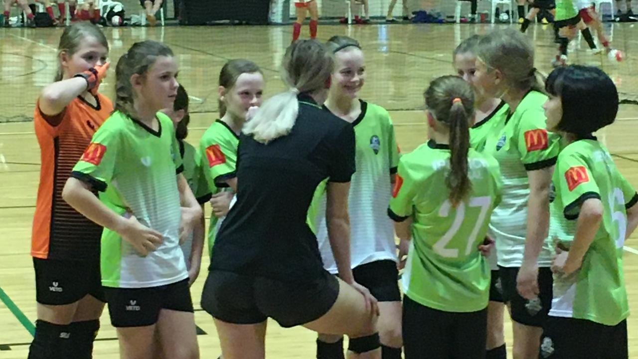 Ipswich Futsal Academy under-13 girls listen intently to instructions during a game.