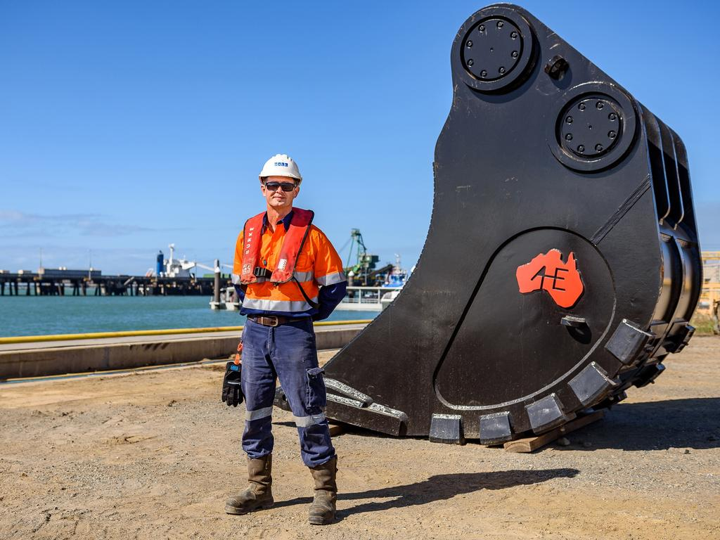 Hall Contracting deckhand Graeme Higgins inspects a custom backhoe bucket that has been designed for excavating hard rock.