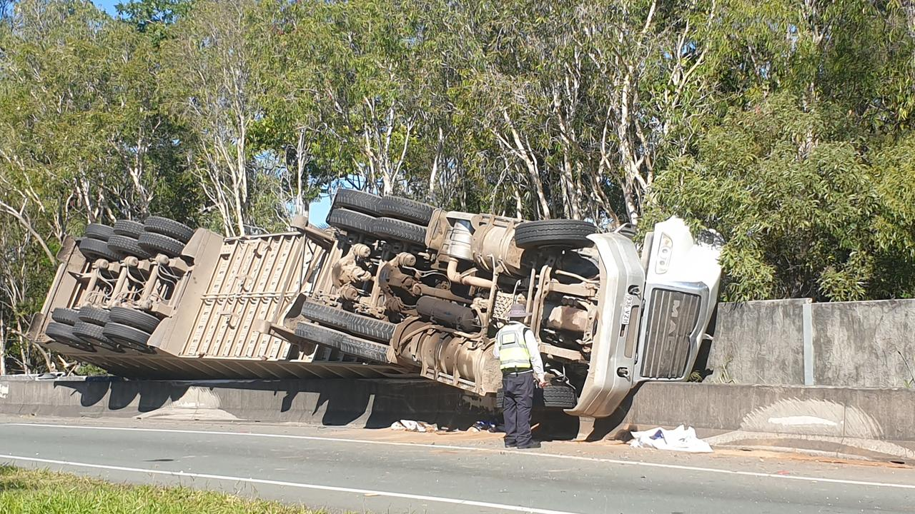 A semi-trailer filled with mulch has rolled on its side along the Pacific Motorway this morning, spilling mulch and petrol. Photo: Jodie O'Brien
