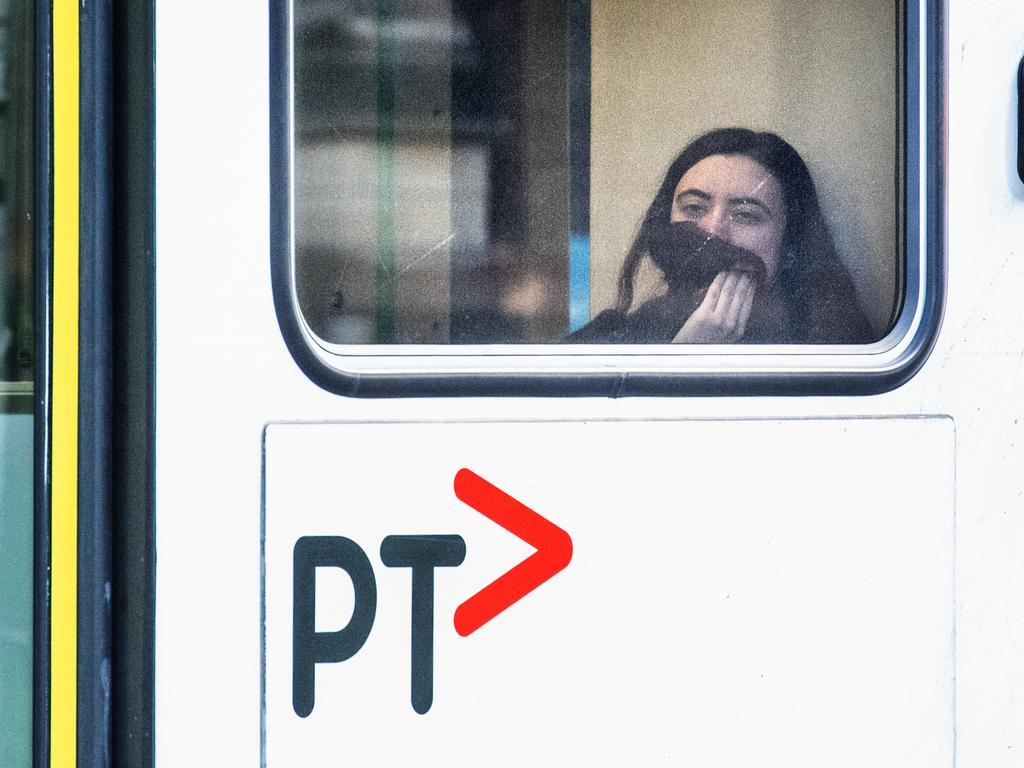 A woman covers her face on a Swanston Street tram. Picture: Tony Gough