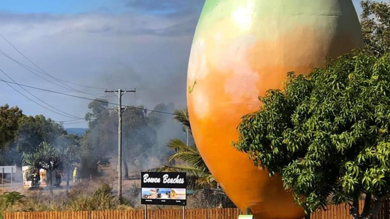 The Big Mango on the Bruce Highway at Bowen shrouded in smoke due to a nearby hay bale fire. Photo: Bowen Tourism & Business