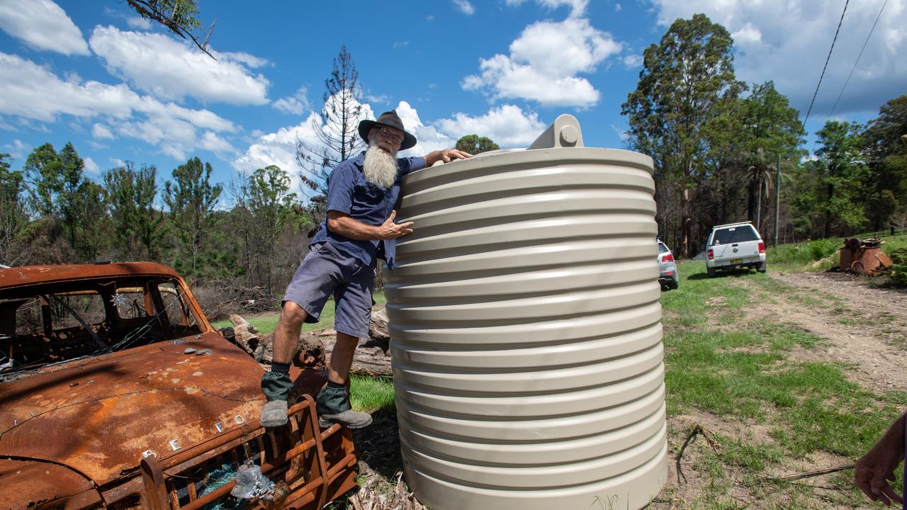 RAINWATER: Ian Watson gets a water tank from Lions Clubs. Pic Trevor Veale