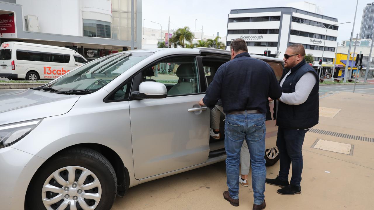 The minders helping Arthur Alex into the van. Picture: Glenn Hampson