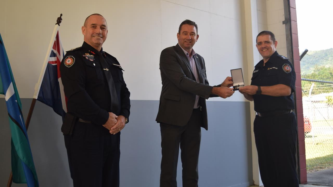 (From left) QFES assistant commissioner for central region Darryl King and Fire and Emergency Services Minister Craig Crawford present a QFES medal to Airlie Beach station officer Kevin Tomas for his longstanding service.
