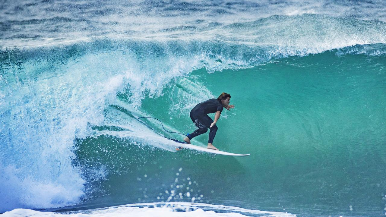 A surfer takes on a large wave at Coolum. Photo: Lachie Millard