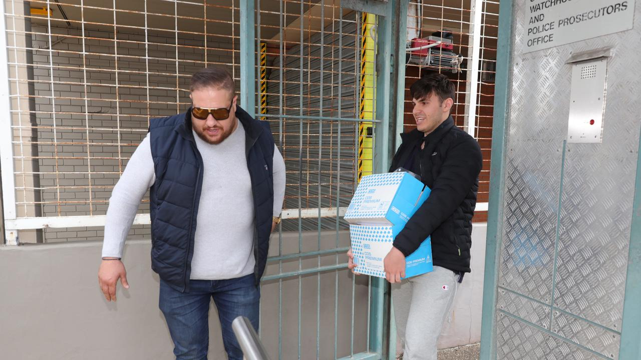A minder ushers Arthur Alex (right), who is accused of being part of a tax fraud syndicate, leaves Southport Watchhouse. Picture: Glenn Hampson