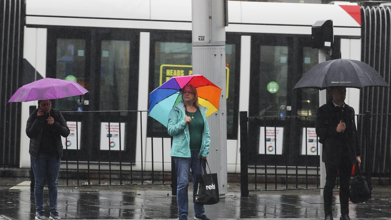 Commuters in the rain on Monday morning on Elizabeth Street, near Central Station. Picture: Dylan Robinson